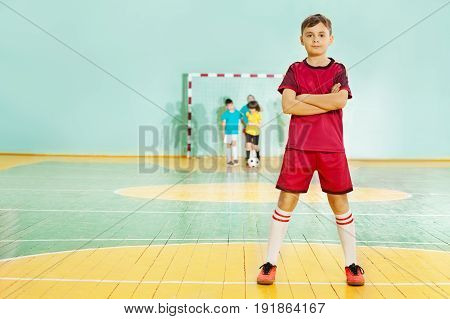 Portrait of 12 years old boy, football player in uniform, standing in sports hall with his arms folded
