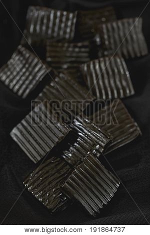 Black liquorice candy sweets on black background