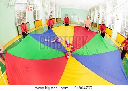 Group of preteen girls forming a circle around rainbow parachute full of colorful balls
