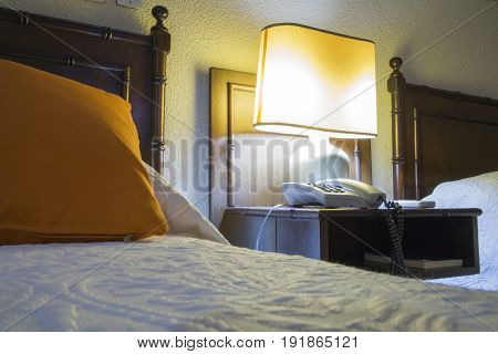 Cheap Hostel with beds, nightstand and lamp at night