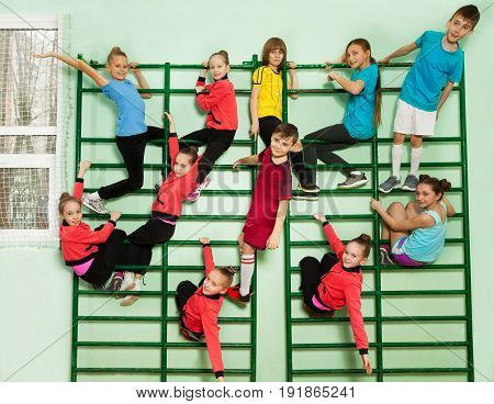Group of sporty girls and boys in sportswear climbing on wall-mounted ladder of school gymnasium
