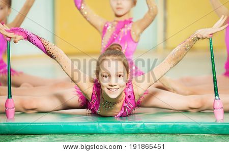 Portrait of beautiful preteen girl doing rhythmic gymnastics with Indian clubs, sitting on split on gym mat