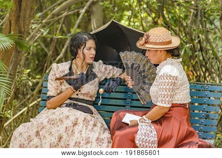 GUAYAQUIL, ECUADOR, MAY - 2016 - Two adult young actresses with 19th century clothes chatting at historic park located at samborondon neighborhood Guayaquil Ecuador
