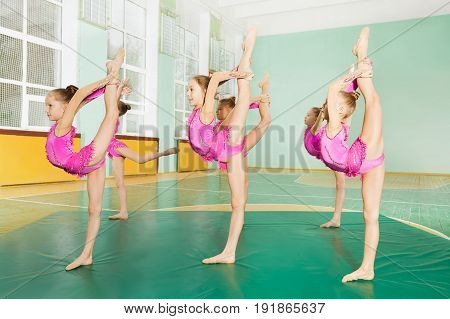 Side view portrait of 11-12 years old girls making balance, practicing rhythmic gymnastics in sports hall