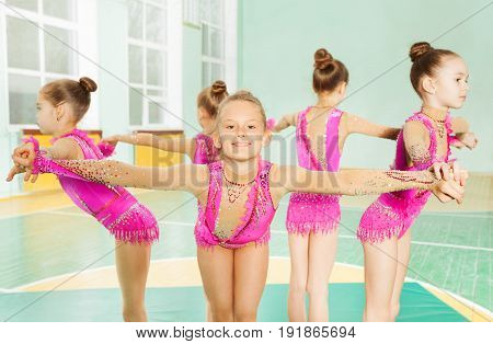 Portrait of beautiful preteen girls in pink leotards, performing rhythmic gymnastics element, forming a circle holding hands