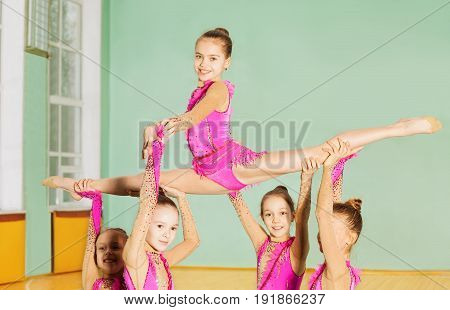 Group of beautiful preteen girls performing rhythmic gymnastics element in sports hall