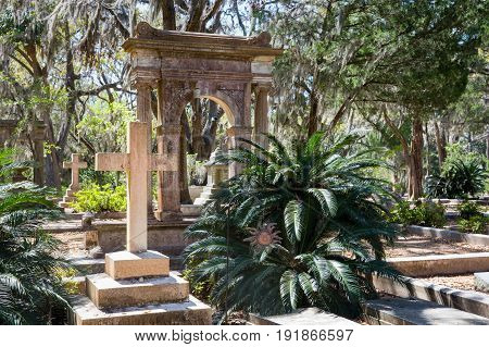 Historic Bonaventure Cemetery in Savannah GA. Serene scene with prominent cross in the foreground lush vegetation and Spanish moss.