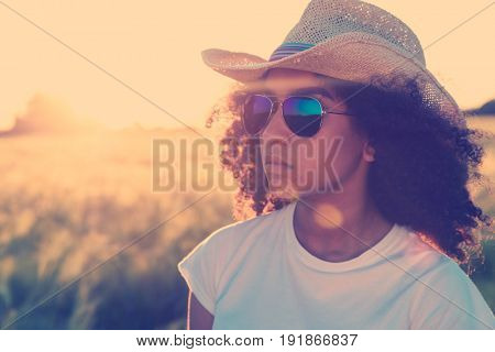 Instagram filter style photo beautiful happy mixed race African American female girl teenager young woman wearing reflective aviator sunglasses and cowboy hat in cornfield at golden sunset or sunrise
