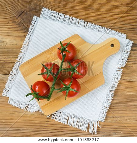 Fresh red ripe tomatoes cherry with water drops on branch on wooden background with rustic chopping board in center and white linen napkin. Top view, copy space