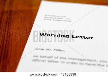 A letter on a wooden table - warning