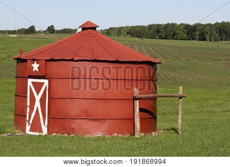 Vintage red grain bin on a green farmland pasture