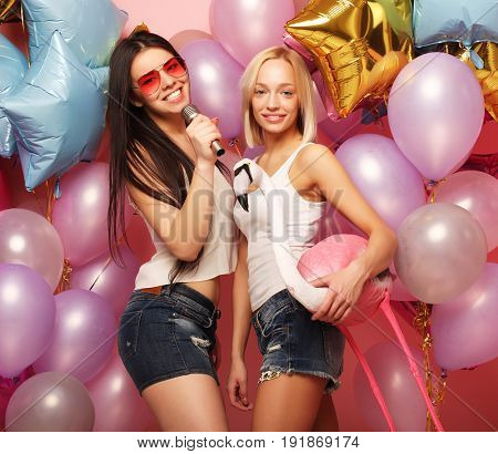 lifestyle, party  and people concept: Happy girls with microphon