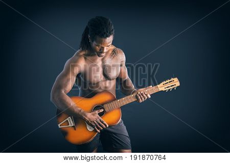 Portrait of muscular topless young black man playing guitar on dark background