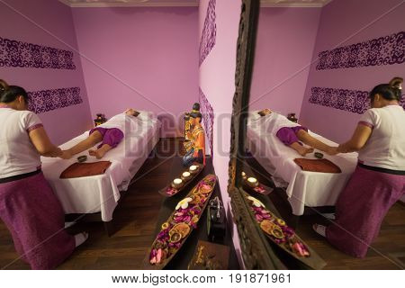 Woman does thai massage for woman on couch in spa room with mirror