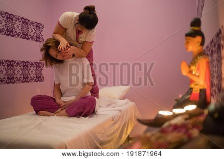 Masseur does thai massage for young woman on couch in spa salon with candles