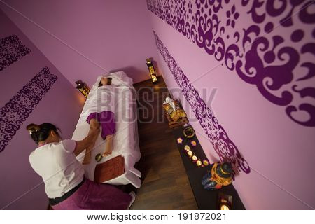 Masseur does thai massage for woman on couch in spa room, top view