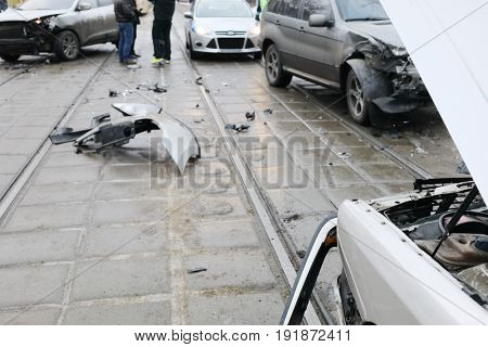 Group car accident with many damages on street, people and police car out of focus at winter