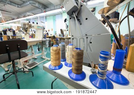 Workshop with sewing machines of modern shoes factory, focus on bobbins, people out of focus