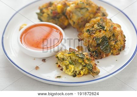 Sweetcorn fritters with sweet chilli dip on white plate