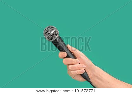 Interviewer Or Reporter With Microphone In Hand On Green Background