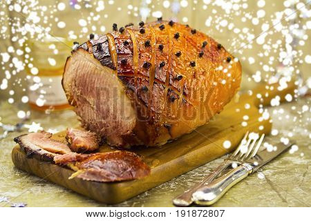 Roasted ham with apricot glaze and cloves on wooden board
