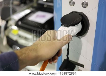 Male hand holds white refueling hose at electric station, car out of focus