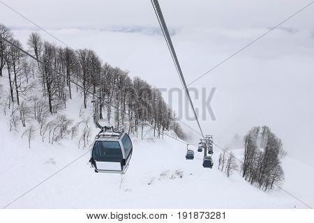 Cableway at winter day in ski resort in mountains in fog in Krasnaya Polyana village, Sochi, Russia