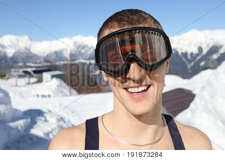 Half-naked skier in ski goggles smiles on mountain in ski resort at winter day