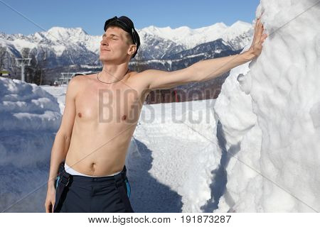 Half-naked skier enjoys sunlight on mountain in ski resort at winter day
