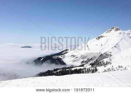 Mountains with fog in ski resort, Krasnaya Polyana, Sochi, Russia in winter sunny day