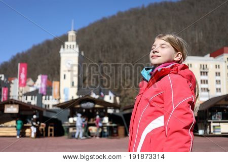 Girl in ski suit stands with closed eyes on square in ski resort with mountains, Krasnaya Polyana, Sochi, Russia