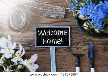 Sign With English Text Welcome Home. Sunny Spring Flowers Like Grape Hyacinth And Crocus. Gardening Tools Like Rake And Shovel. Hemp Fabric Ribbon. Aged Wooden Background
