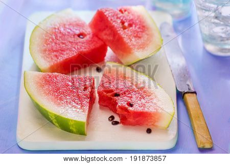 Four watermelon chunks on white board with knife