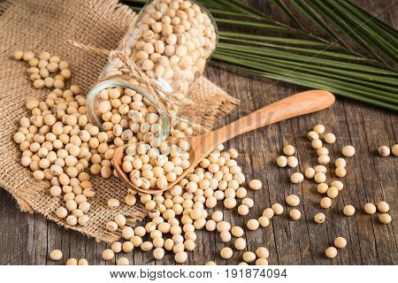 Soybeans in glass bottles on old wood background