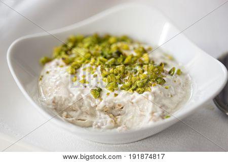 Yoghurt porridge with pistachios in white bowl