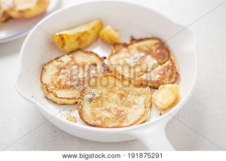 Apple pancakes on white pan with icing sugar