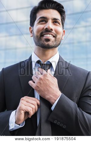 Arabic serious smiling happy successful positive businessman or worker in black suit with beard standing in front of an office building and straightens his tie with his hands.