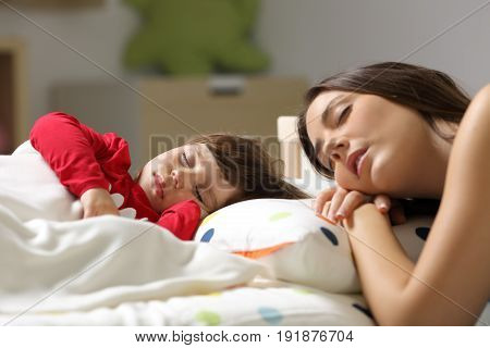 Tired mother and toddler sleeping together in a bed in the bedroom at home