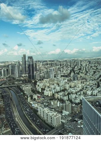 Tel Aviv from a bird-eye view on blue cloudy sky background