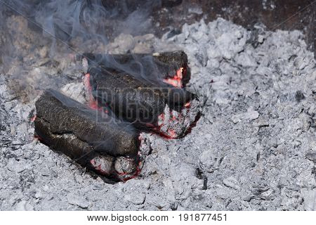 Smoldering sunflower shell biomass briquettes with smoke