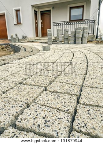 Pavement path laid from light creme concrete pavement blocks with mineral topping