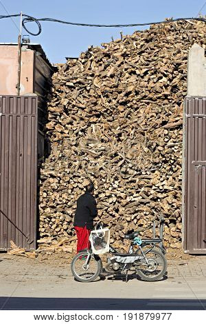 Man standing by the pile of wood, Marrakech, Morocco