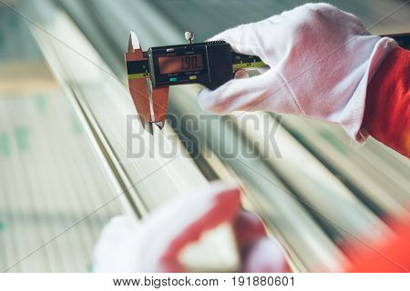 worker measuring aluminum product with vernier caliper in a plant.