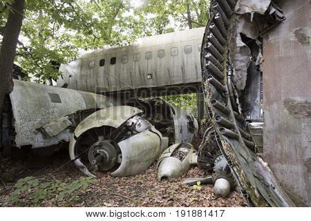 Wreckage of crashed plane in wooded junkyard.