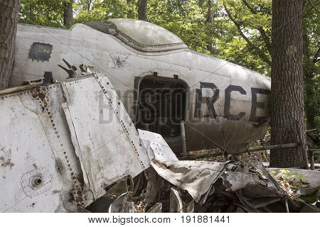 Wreckage of US Air Force fighter jet in trees of junkyard.