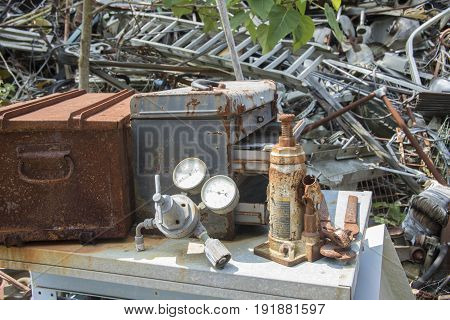 Rusting tools and toolboxes on table in junkyard.