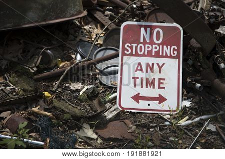No stopping sign in pile of trash on ground.