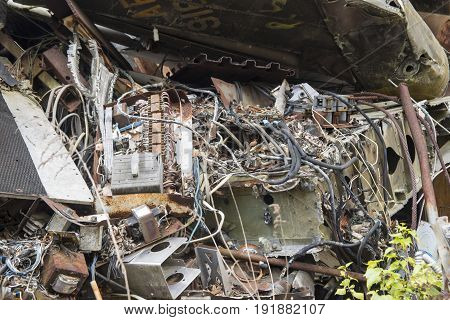 Wires and electronics inside wrecked airplane in junkyard.