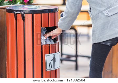 side view of man hand throw rubbish into dustbin in city streetChina.