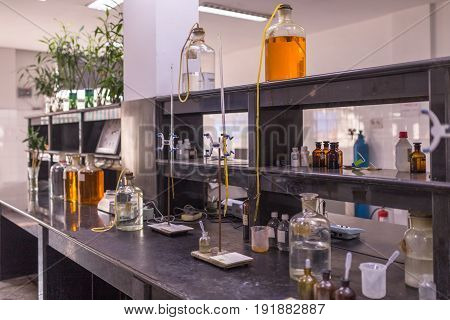 detail shot of beakers and equipment on table in factory laboratory.